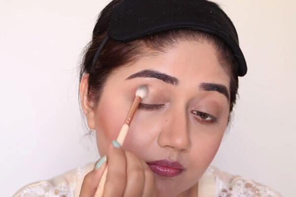 applying brown shade on eye