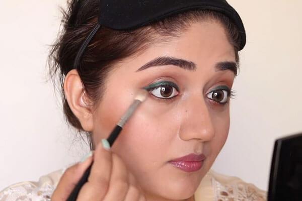 eye makeup by applying brown eye shadow