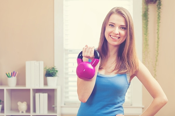 One-arm kettlebell push press—using a heavy water container